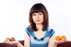 Girl holds a tangerine and kiwi Royalty Free Stock Images