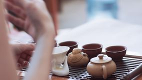 The girl holds a tea ceremony, teaches how to brew tea. On the table are cups, figurine and teapot.  stock footage