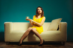 Girl holds tea cup sitting on sofa Stock Images