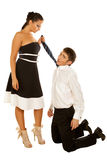 Girl holds the tie guy kneeling Royalty Free Stock Image