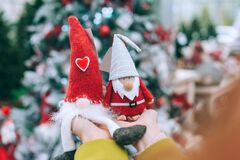 The girl holds Tomte and the gnome in her arms. Against the background of a Christmas tree in the store