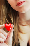 Girl holds a toy heart Stock Images