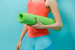 Girl holds twisted fitness mat Stock Image