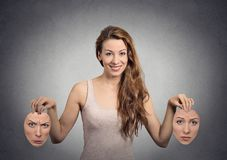 Girl holds two face masks. Portrait beautiful happy girl holds two masks  grey wall background. Human face expressions, emotions, feelings, bipolar state of mind Stock Photo