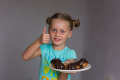 A girl holds up a finger showing some delicious cakes on a plate Stock Photography