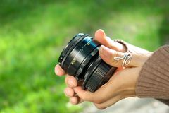 The girl holds a vintage lens in hand royalty free stock photos