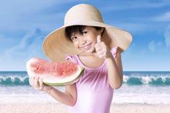 Girl holds a watermelon on the beach Stock Photos