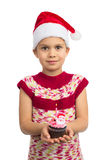 Girl with Holiday Cupcake. Beautiful young girl in Santa hat holds colorful cupcake with toy Santa on top of it, isolated stock photo