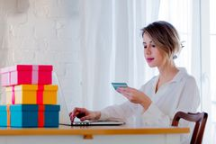 Girl with holiday gifts and laptop computer holding a credit card royalty free stock photo