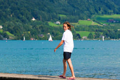 Girl on holiday walking down a pier Stock Images