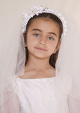 Girl in Holy Communion Dress. Girl celebrating her First Communion. She is looking straight into the camera, with big beautiful green eyes Vertical photo Royalty Free Stock Photo