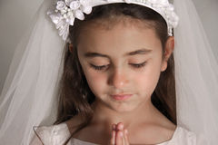 Girl in Holy Communion Dress praying. Girl celebrating her First Communion. She is holding her hands together in front of her, praying. She looks down on her Royalty Free Stock Photo