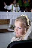 Girl in holy communion dress and veil. A young child doing her catholic first holy communion attending mass wtih a priest by the altar royalty free stock image