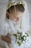 Girl in holy communion dress and veil. A young child praying dressed up for her first holy communion holding a candle stock photos