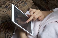 A girl in a home bathrobe lying on the couch working with a tablet. Royalty Free Stock Photography