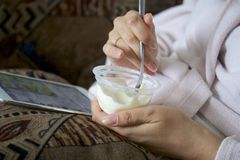 A girl in a home bathrobe lying on the couch working with a tablet. At the same time he eats yogurt. A girl in a home bathrobe lying on the couch working with a stock photos