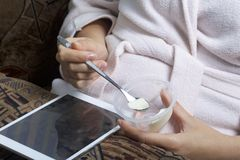 A girl in a home bathrobe lying on the couch working with a tablet. At the same time he eats yogurt. Royalty Free Stock Photography