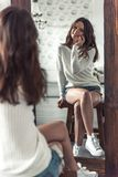 Girl at home. Beautiful young girl in casual clothes is talking on the mobile phone, looking in the mirror and smiling while sitting on chair Stock Photo