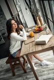 Girl at home. Beautiful young girl in casual clothes is writing in the notepad, holding a glass of juice and smiling while sitting at the wooden table at home Royalty Free Stock Image
