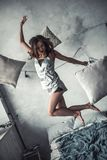 Girl at home. Beautiful young girl in pajama is laughing while jumping on bed at home Stock Photo