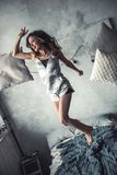 Girl at home. Beautiful young girl in pajama is laughing while jumping on bed at home Royalty Free Stock Photos