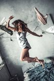 Girl at home. Beautiful young girl in pajama is laughing while jumping on bed at home Stock Photos