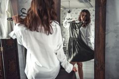 Girl at home. Beautiful young girl in white shirt and panties is holding a dress while looking in the mirror Royalty Free Stock Images