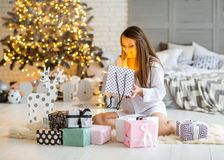 Girl at home on christmas looking at gifts under a Christmas tre. E Stock Photography