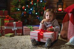 Girl at home with a Christmas tree, presents and candles celebra. Little girl at home with a Christmas tree, presents and candles celebrating christmas Royalty Free Stock Images
