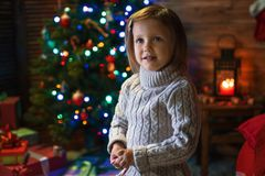 Girl at home with a Christmas tree, presents and candles celebra. Little girl at home with a Christmas tree, presents and candles celebrating christmas Stock Images