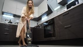 Girl in home clothes vacuuming in the kitchen. 4K Slow Mo stock video footage