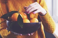 Girl at home holding bowl with winter tangerines. Girl at home holding wooden bowl full of fresh winter tangerines Stock Photos