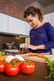 Girl in home kitchen looking recipe with a Stock Photography