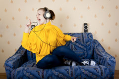 Girl at home listening to music through headphones Royalty Free Stock Photos