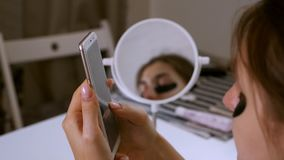 The girl at home monitors the skin around her eyes, cosmetic care, Korean cosmetics. The girl uses the phone.  stock footage