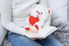 Girl at home reading a book and holding a polar bear toy. stock photo