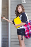 Girl Home From School. A cute teenage girl with book bag and notebook at the door returning from school Royalty Free Stock Photos
