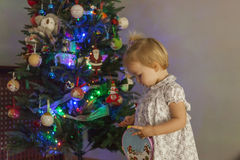Girl at home setting up the christmas tree with lights and ornam Royalty Free Stock Photos
