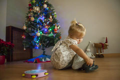 Girl at home setting up the christmas tree with lights and ornam Stock Image