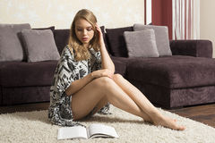 Girl in home sitting on carpet and reading Stock Photo
