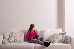 Girl at home sitting on sofa, playing with laptop Stock Photo