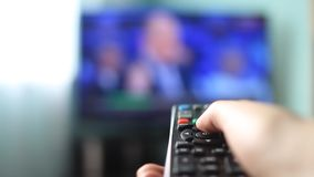 The girl at home switches the remote control channels of the TV, close-up.  stock video