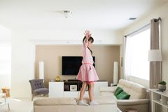 Girl at home on top of furniture stock image