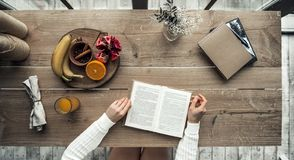Girl at home. Top view of girl sitting at the wooden table and reading, cropped Stock Photos