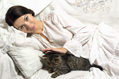 Girl in a homely atmosphere petting a kitten .   Royalty Free Stock Photo