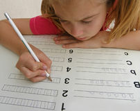 Girl and homework (numbers and types). Female writing's numbers in math homework Stock Photography