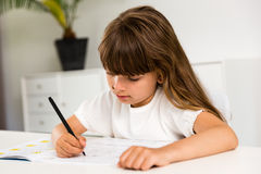 Girl with homework. Young caucasian girl doing her homework while sitting at table Royalty Free Stock Images