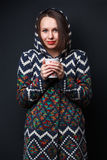 Girl in a hood keeping a cup Royalty Free Stock Image