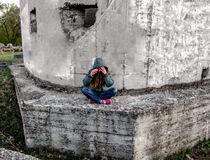 A girl in a hood sits in a lotus pose on a concrete wall. She has long blond hair and she hides her face with her hands Stock Photos