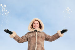 Girl in hood throws hands snow upwards Royalty Free Stock Photography
